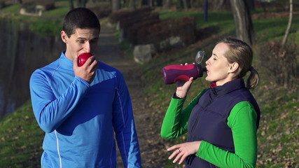 Couple drink and eat apple after workout, crane shot