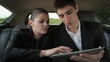 Young business couple working on tablet computer in car