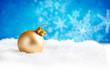 Goldene Weihnachtskugel vor winterlichem Hintergrund