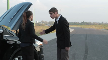 Young couple arguing in front of a broken car