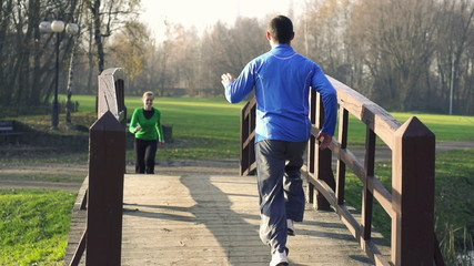 Man and woman jogging in the park, crane shot, slow motion