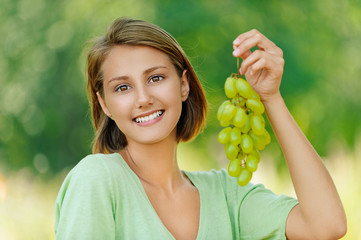young woman with bunch of grapes