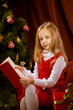 Little girl  reading book near Cristristmas tree