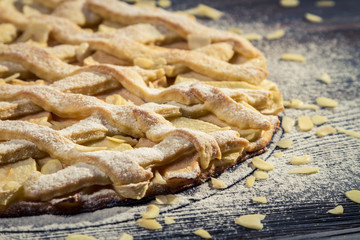 Closeup apple pie with almonds and icing sugar on baking tray