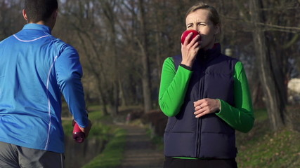 Woman eat apple after workout, man jogging, super slow motion