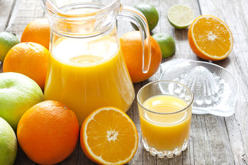 Orange juice with lime grapefruit and squeezer on wooden boards