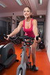 Beautiful girl exercising on the bicycle in the gym