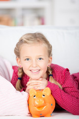 kind liegt mit sparschwein auf dem sofa