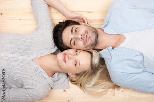 lächelndes paar liegt auf dem fußboden