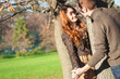 Romantic young couple playing outdoors in autumn park.