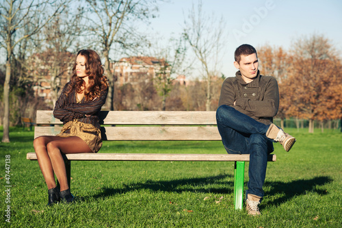 Angry young couple sitting away outdoors on a bench.