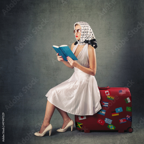Retro woman with sunglasses and suitcase reading book