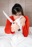 Terrified woman in bed holding knife for self defense