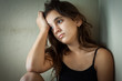 Sad hispanic girl sitting in a dark corner