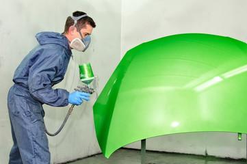 Worker painting green car bonnet.