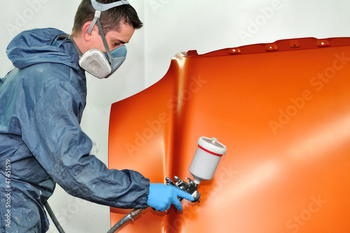 Worker painting orange car bonnet.