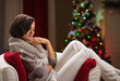 Calm young woman relaxing on chair in front of Christmas tree