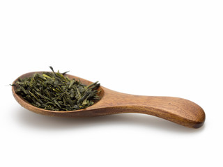 Green tea leaves and wooden scoop white background