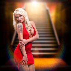 junge blonde im roten Minikleid am Fuße einer Treppe