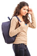 A sad female teenager with a school bag on her back posing