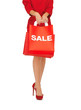 woman on high heels holding shopping bag
