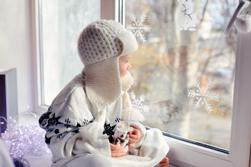 winter boy sitting by the window in a white knitted cap