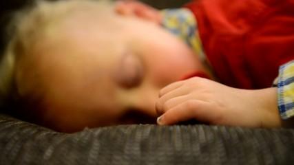 Kleinkind mit Schnuller schläft auf dem Sofa, Kamerafahrt