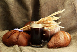 tankard of kvass and rye breads with ears, on burlap background