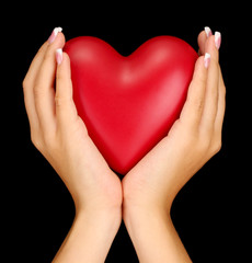 Red heart in woman's hands, on black background close-up