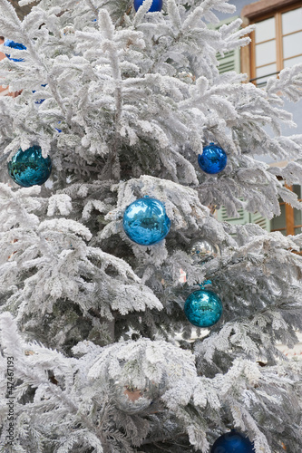 blue christmas balls hanging from a white christmas tree
