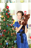 Little girl holding toy near christmas tree