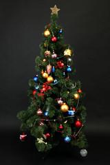 Decorated Christmas tree isolated on black