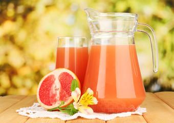 Full glass and jug of grapefruit juice and grapefruits