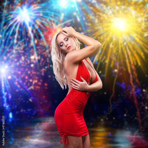 blonde Frau im roten Minikleid vor Feuerwerk