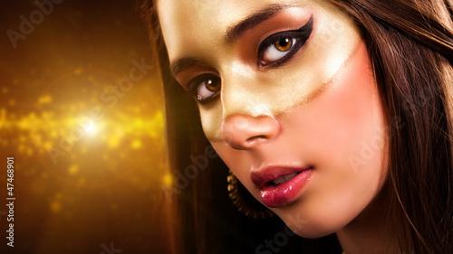 junge Frau mit Goldmaske vor Lichterhintergrund