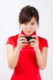 A wear qipao Asian woman, playing mobile games