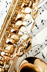 Saxophone keys closeup with score notes in background