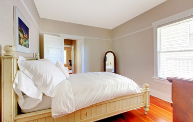 Bright bedroom with white bed and beige walls.