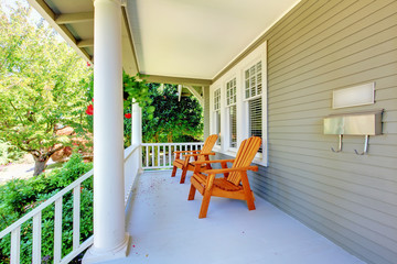 Front porch with chairs and columns.