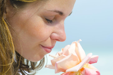 Pretty young girl smelling scent of flower