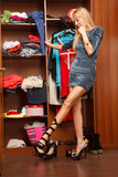 Beautiful young woman stands near her wardrobe  in different sho