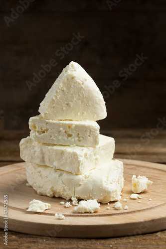 Still life with white cheese on wooden board