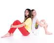 Zwei hübsche Mädchen sitzen Rücken an Rücken
