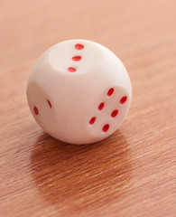 Close-up of a single dice rolling three.