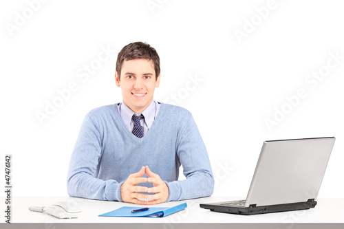Smiling male posing on a desk with laptop and other office staff