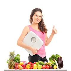 Happy female holding a weight scale behind a pile of different f