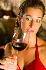 Frau betrachtet Wein Glas im Weinkeller