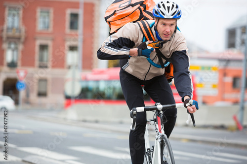 Leinwanddruck Bild Male Cyclist With Courier Delivery Bag Riding Bicycle