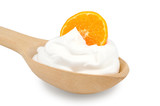Wooden spoon is with creams and slice of tangerine on a white