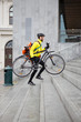 Courier Delivery Man With Bicycle And Backpack Walking Up Steps